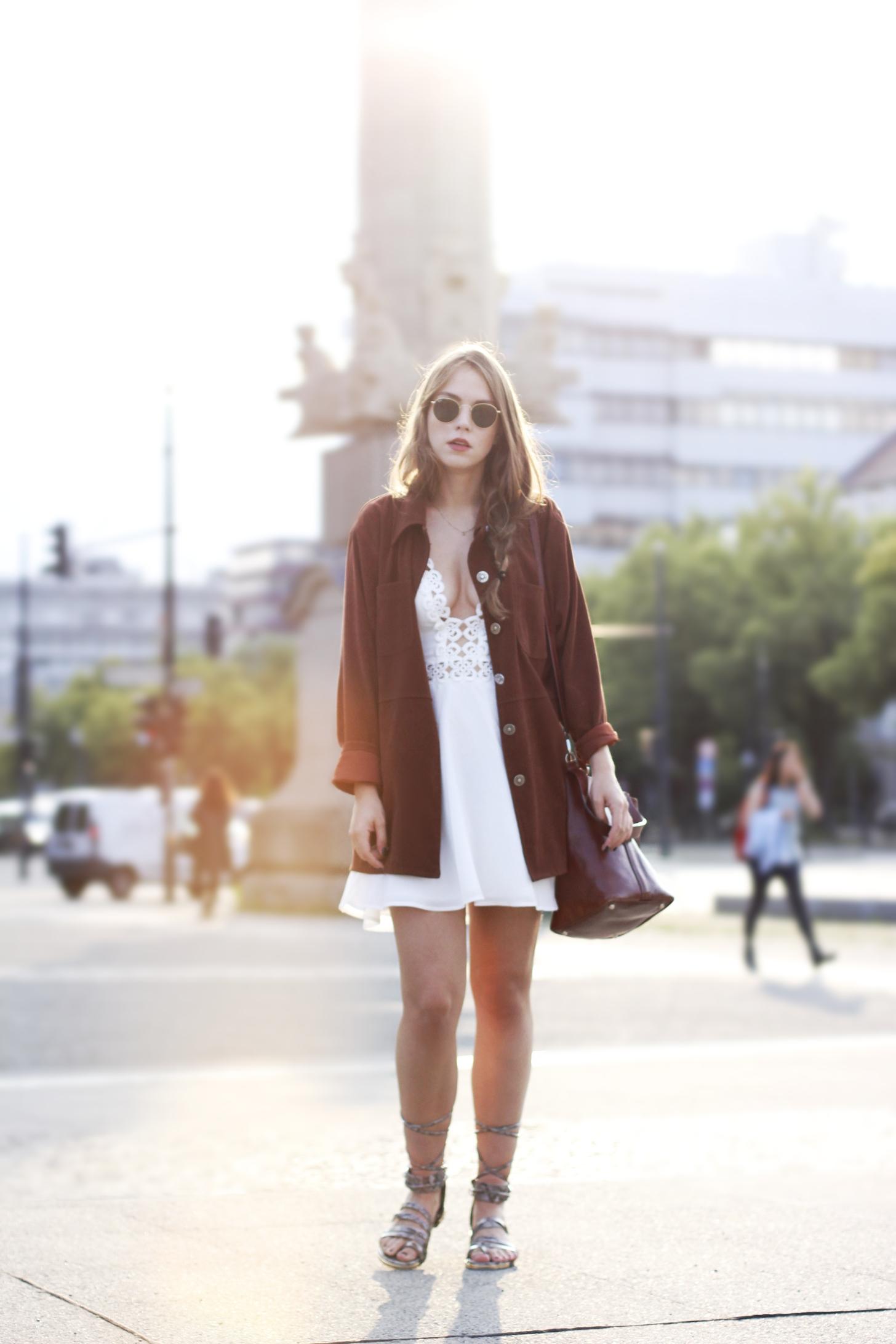 Weißes Kleid mit Gladiatorsandalen und Vintagejacke in rostbraun